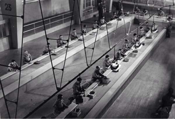 Imagem de um filme do Charlie Chaplin em que os operários trabalham na linha de produção da fábrica.