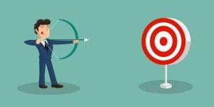 Imagem de um homem com um terno azul e um sapato marrom, com uma flexa na mão e tentando acertar o alvo na sua frente. Essa imagem tenta simbolizar o planejamento estratégico eficaz.