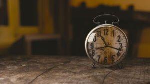 Relógio antigo encima de uma mesa, simbolizando o atraso na entrega de relatórios de não conformidades.