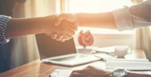 Cliente e fornecedor em um aperto de mãos firme e confiante confiante.