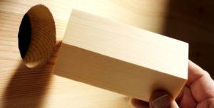 Pessoa tentando encaixar um cubo de madeira em um espaço circular.