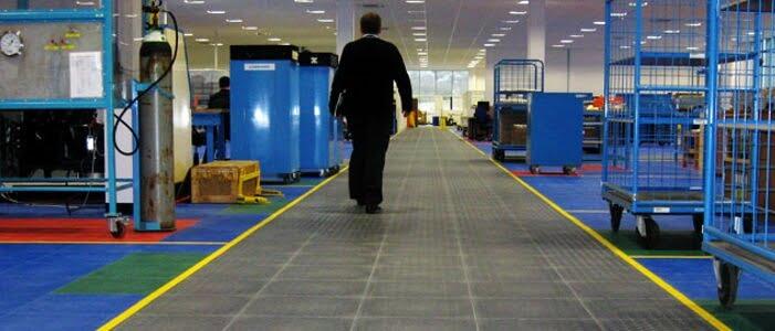 Homem caminhando por uma fábrica em que o ambiente está limpo e organizado, dessa forma estimula o engajamento dos colaboradores.