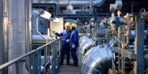 Dois colaboradores industriais debatem os sistema de produção, realizando o 8.1 Planejamento e controle operacionais.
