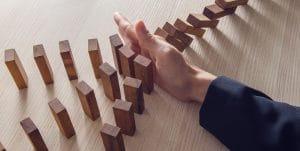 Imagem de uma sequência de dominós em queda sendo interrompida por uma mão, representando a importância de saber como fazer Planos de Contingência e da Gestão de Riscos.