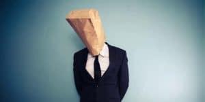 Imagem de um homem de terno com um saco de pão na cabeça, simbolizando a apatia não quebrada pelas ações de engajamento.