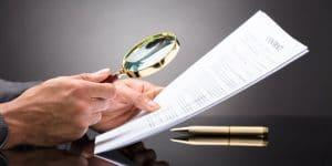 Imagem de uma pessoa analisando constatações de auditoria com uma lupa.