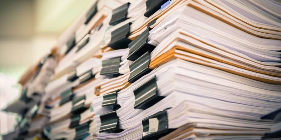 Imagem de muitos documentos empilhados representando a incrível arte de fazer fluxogramas inúteis.