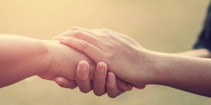 Imagem de duas pessoas com as mãos dadas, simbolizando a empatia como ferramenta da qualidade.