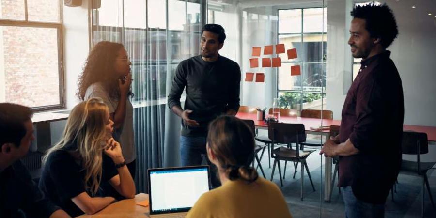 imagem com 3 homens e 3 mulheres conversando em uma empresa. Uma das mulheres está digitando no notebook enquanto os outros prestam atenção no que um rapaz fala. Essa imagem simboliza o artigo sobre criar uma gestão a vista eficaz.
