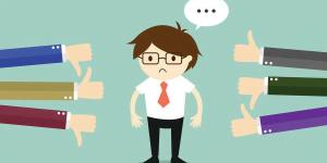 Imagem com um bonequinho de terno e gravata recebendo um feedback negativo e alguns positivos. Essa imagem simboliza o artigo sobre zero defeitos
