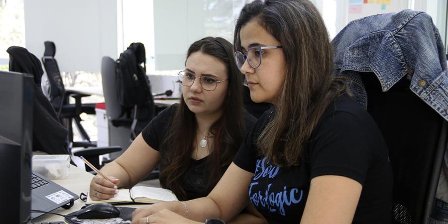 imagem da Camila (líder) com a Fernanda (liderada). Essa imagem simboliza o artigo sobre A relação entre liderança, falha de processos e gestão de competências.