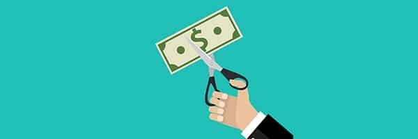 Imagem de uma mãozinha cortando um dinheiro. Essa imagem simboliza o artigo sobre reduzir custos de metrologia.