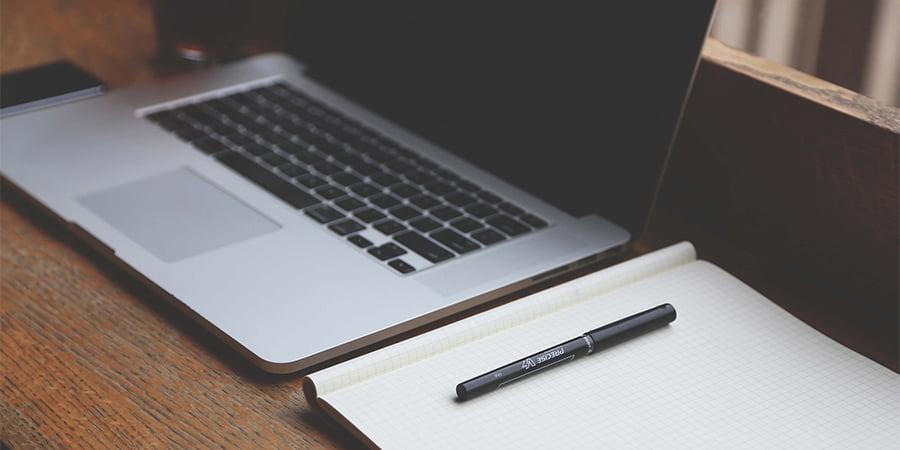imagem de um computador com um bloco de notas e uma caneta ao lado. Essa imagem simboliza o artigo sobre ação imediata